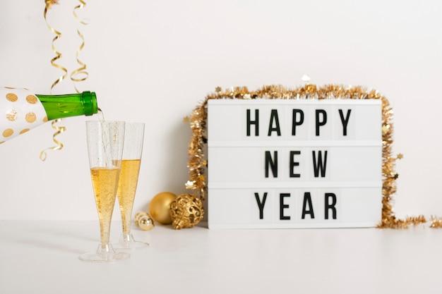 Segno di felice anno nuovo con bicchieri di champagne Foto Gratuite