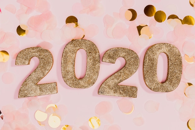 Segno di nuovo anno con coriandoli oro e rosa Foto Gratuite