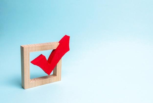 Segno di spunta in legno rosso per il voto sulle elezioni su sfondo blu. Foto Premium