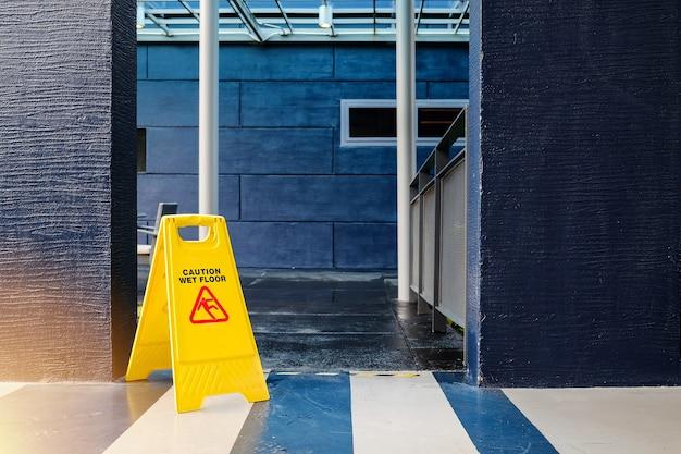 ํ segno giallo attenzione pavimento bagnato con edificio blu