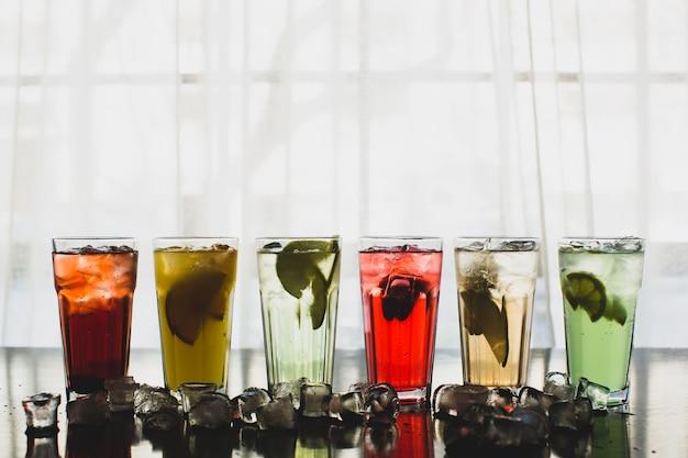Sei bicchieri di cocktail di frutta circondati da cubetti di ghiaccio Foto Gratuite