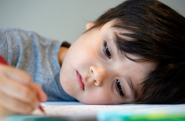 Selctive focus ragazzo bambino solitario sdraiato a testa in giù sul tavolo con la faccia triste, ritratto emotivo di cinque anni vecchio ragazzo annoiato con compiti a scuola, bambino viziato Foto Premium