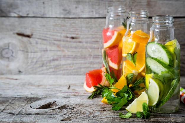 Selezione di acqua infusa in bottiglie di vetro, fondo di legno rustico Foto Premium