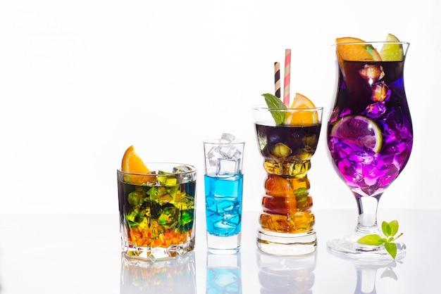 Selezione di colorate bevande festive, bevande alcoliche e cocktail in eleganti bicchieri su bianco Foto Premium