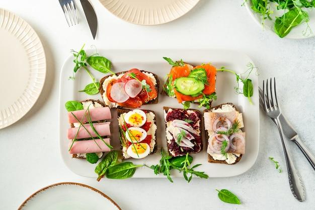 Selezione di smorrebrod danese sandwich aperti su un piatto, foglie di insalata, piatti, posate sul tavolo bianco Foto Premium