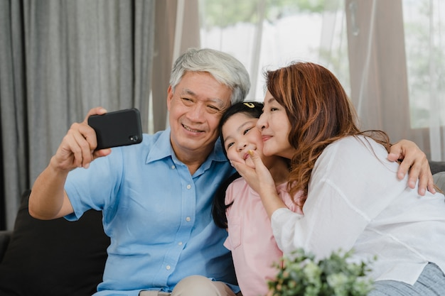 Selfie asiatico dei nonni con la nipote a casa. il tempo felice della famiglia di cinese, del nonno e della nonna senior si rilassa facendo uso del telefono cellulare con il bambino della ragazza che si trova sul sofà nel concetto del salone. Foto Gratuite