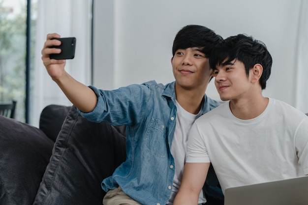 Selfie divertente delle giovani coppie gay romantiche dal cellulare a casa. il maschio asiatico dell'amante felice si rilassa il divertimento facendo uso sorridente del telefono cellulare della tecnologia prende una foto insieme mentre si trova sofà in salone. Foto Gratuite
