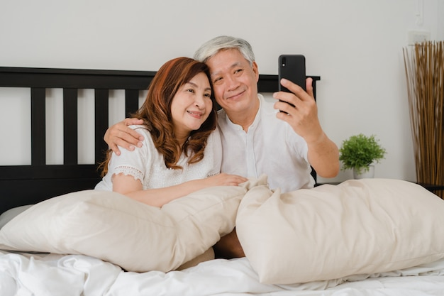 Selfie senior asiatico delle coppie a casa. i nonni cinesi senior asiatici, il marito e la moglie che utilizzano il selfie usando felice del telefono cellulare dopo svegliano la menzogne sul letto nel concetto della camera da letto a casa di mattina. Foto Gratuite