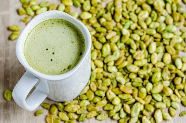 Semi commestibili dello spuntino del fagiolo del giacinto e del latte del tè verde su legno Foto Premium