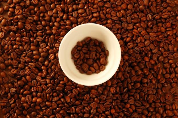 Semi di caffè marrone dorato, intorno alla tazza bianca Foto Premium