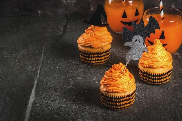 Semplice idea di scherzetto divertente per halloween: torte di zucca con panna con decorazioni a forma di simboli natalizi - fantasma strega pipistrello su sfondo nero Foto Premium