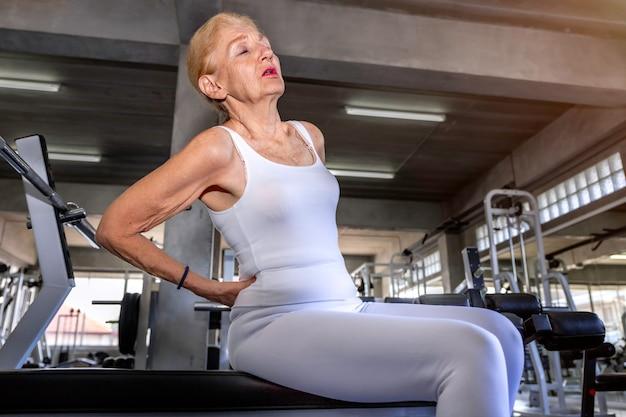 Senior donna caucasica mal di schiena durante l'allenamento in palestra. Foto Premium