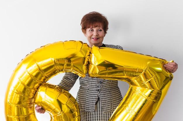 Senior donna festeggia il suo birthay a casa con torta, ballons e coriandoli Foto Premium