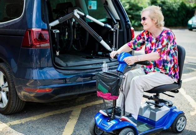 Senior donna su una sedia a rotelle elettrica Foto Premium
