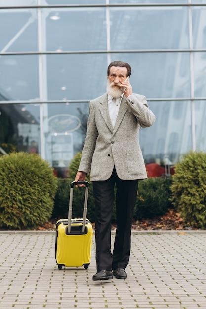 Senior uomo con la barba grigia con la valigia per il trasporto e la mappa della città sta camminando lungo l'edificio dell'aeroporto. sta guardando da parte pensieroso. copia spazio sul lato destro Foto Premium