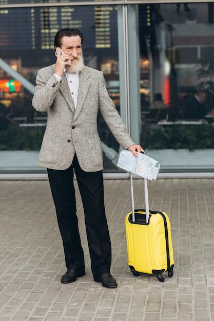 Senior uomo con la barba grigia con valigia e mappa della città di trasporto sta prendendo per telefono e camminando lungo l'edificio dell'aeroporto. sta guardando da parte pensieroso. copia spazio sul lato destro Foto Premium