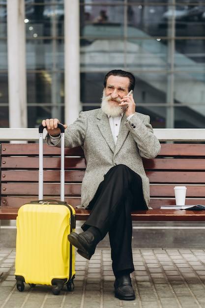 Senior uomo con la barba grigia si siede su una panchina con una valigia e una mappa della città e parla al telefono presso l'edificio dell'aeroporto Foto Premium
