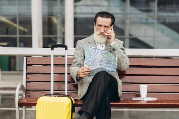 Senior uomo con la barba grigia si siede su una panchina con una valigia, guarda la mappa della città e il telefono all'edificio dell'aeroporto Foto Premium