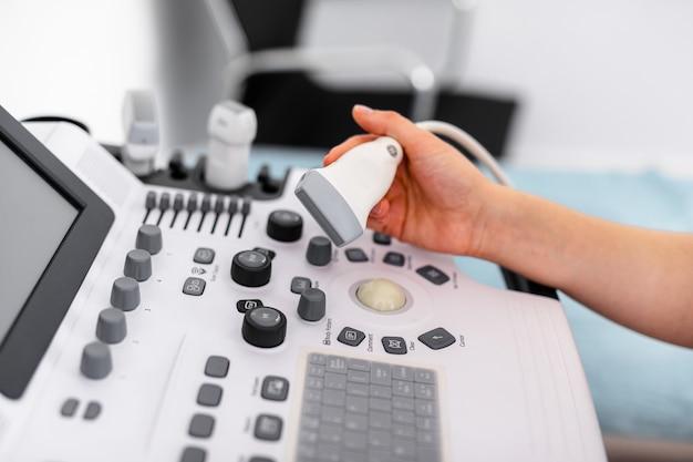 Sensore ad ultrasuoni del moderno scanner ad ultrasuoni nelle mani del medico di giovane donna Foto Premium