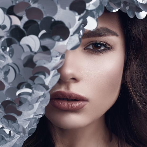 Sensuale bella donna bruna in un abito di moda lucido di paillettes Foto Premium