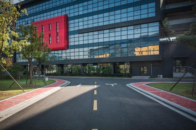 Sentiero per pedoni vuoto con cielo nuvoloso esterno e blu moderno dell'edificio per uffici durante l'alba Foto Premium