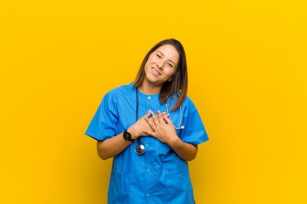 Sentirsi romantici, felici e innamorati, sorridendo allegramente e tenendosi per mano vicino al cuore isolato contro il muro giallo Foto Premium