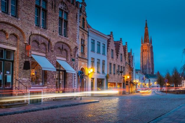 Serata per le strade di bruges dopo la pioggia. vista della notte onze lieve. vrouw brugge sullo sfondo di un cielo blu serale. belgio. Foto Premium