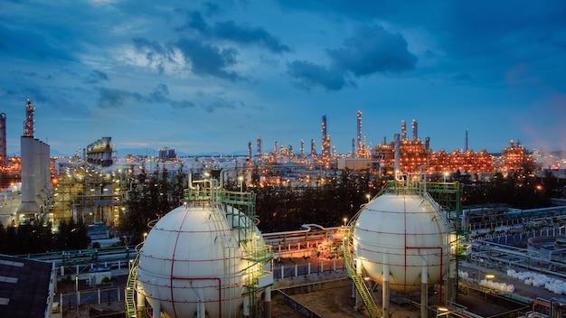 Serbatoi e conduttura della sfera di stoccaggio del gas nell'impianto industriale della raffineria di petrolio e gas con la proprietà di industria di illuminazione di scintillio al crepuscolo Foto Premium