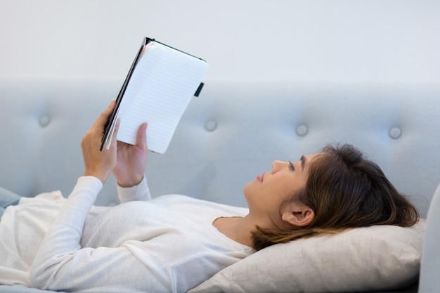 Serena ragazza rilassata sdraiata sulla schiena e leggendo il libro Foto Gratuite