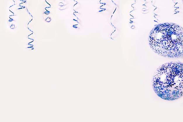 Serpentina blu e palloncini con coriandoli su sfondo chiaro. Foto Premium
