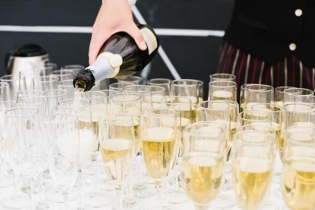 Server riempiendo bicchieri di champagne Foto Gratuite