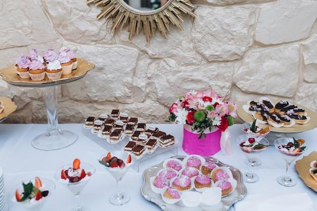 Servito un tavolo da bar di una varietà di dolci come tiramisù, bignè e cupcakes Foto Gratuite