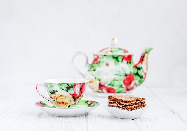 Servizio da tè colorato e torta su un tavolo di legno Foto Premium