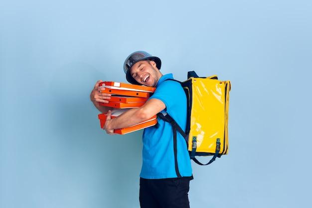 Servizio di consegna senza contatto durante la quarantena. l'uomo consegna cibo e borse della spesa durante l'isolamento. emozioni del fattorino isolate sul blu Foto Gratuite