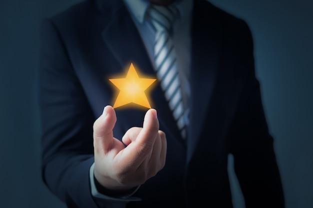 Servizio eccellente e migliore esperienza cliente o buon cliente, uomo d'affari che mostra la valutazione a stelle o obiettivo su sfondo blu scuro Foto Premium