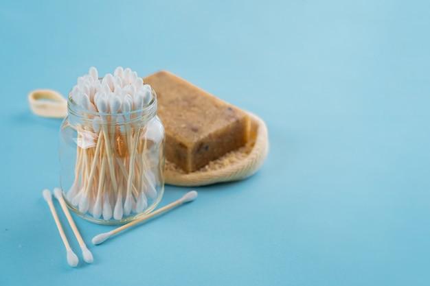 Set da bagno - spugna luffa, orecchie di bastoncini di bambù sulla superficie blu. concetto meno spreco Foto Premium