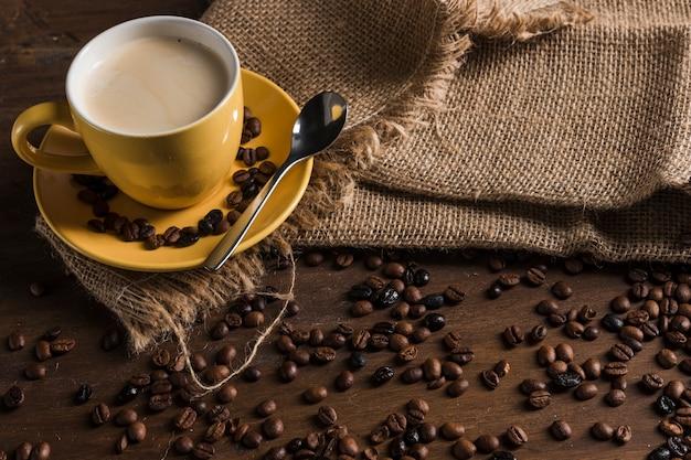 Set da caffè su tela di sacco vicino a chicchi di caffè Foto Gratuite