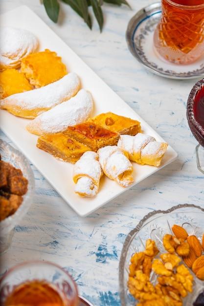 Set da tè con varietà di noci tradizionali, limone, confettura e dolci serviti sulla tovaglia bianca Foto Gratuite