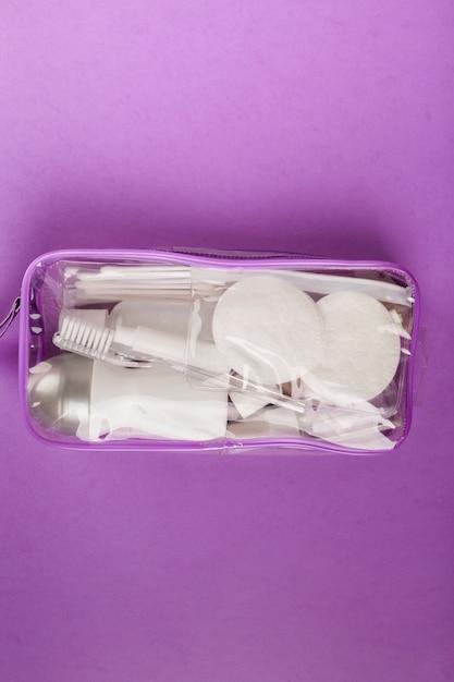 Set da viaggio con piccola bottiglia, in sacchetto trasparente per cosmetici su viola. vista dall'alto Foto Premium