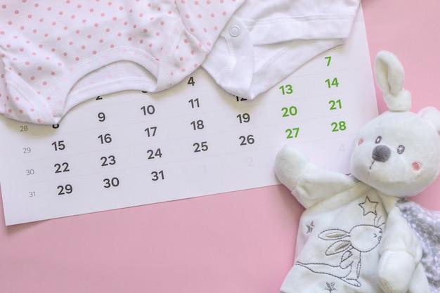 Set di accessori neonato in previsione del bambino - calendario, vestiti per bambini, giocattoli. Foto Premium