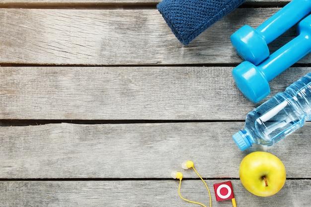 Set di accessori sportivi per il fitness con attrezzi ginnici su legno grigio. Foto Premium