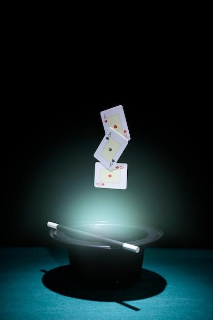 Set di assi che giocano a carte a mezz'aria sopra il cappello nero illuminato Foto Gratuite