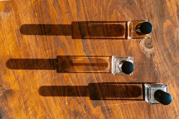Set di bottiglie di profumo su una luce intensa con le ombre Foto Premium