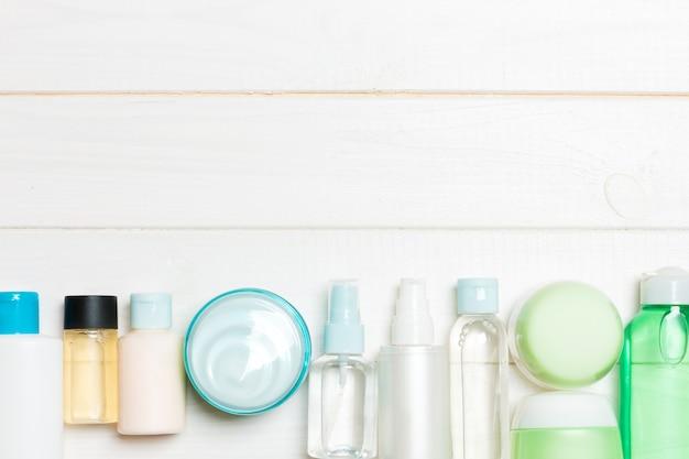 Set di bottiglie e vasetti di crema e cosmetici su legno. cura del corpo con spazio vuoto r Foto Premium