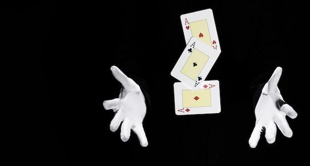 Set di carte da gioco degli assi a mezz'aria tra le mani del mago Foto Gratuite