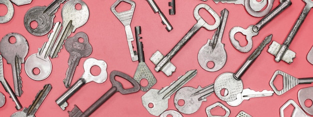Set di chiavi sulla superficie rosa Foto Premium