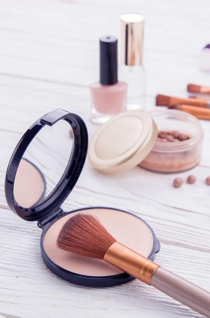 Set di cosmetici con pennelli per il trucco. polvere, smalto e profumo Foto Premium