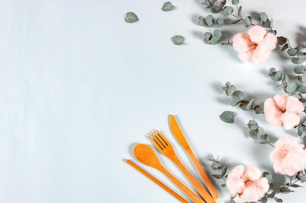 Set di cucchiaio in legno naturale eco, forchetta, cannucce per coltello da bere, foglie di eucalipto e fiori di cotone Foto Premium