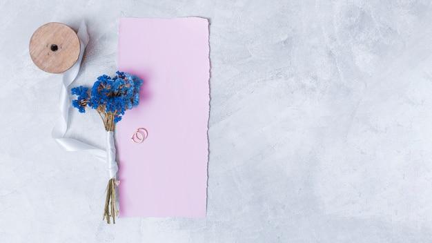 Set di fiori vicino a carta, anelli e fettuccia di nastro Foto Gratuite