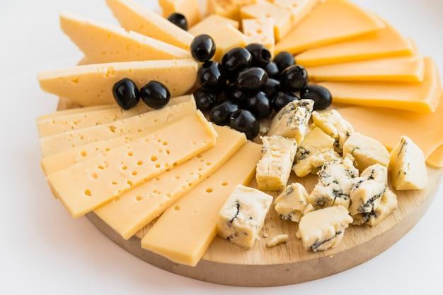 Set di formaggio fresco e olive sul tagliere di legno Foto Gratuite